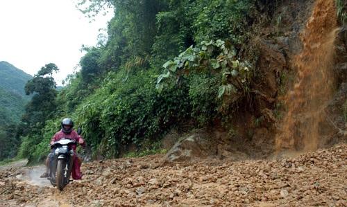 Người dân địa phương vượt qua khu vực sạt lở do trận mưa gây ra...