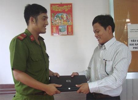 Thượng sĩ Phương (trái) trả lại máy tính xách tay cho anh Hoàng