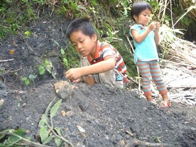 Trẻ em thôn 3 Tiên An chơi đùa bên vùng đất đen. Ảnh: N.T.