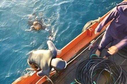 Thợ lặn xuống đáy biển nơi có con tàu ma.