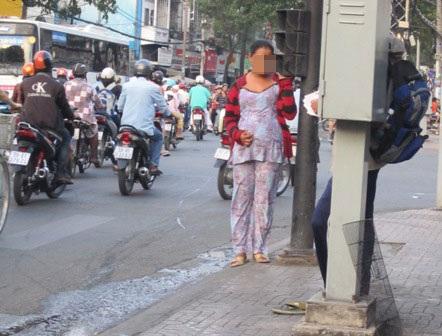 Hình ảnh người phụ nữ mang bầu đứng xin tiền tại giao lộ