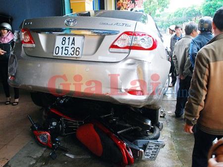 Xe mô tô bị cuốn vào gầm xe ô tô. Ảnh: Nguyễn Giác
