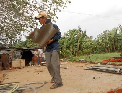 Ông Đặng Oai (thôn Tây, xã An Hải) nhặt mảnh mái vỡ do bão tàn phá