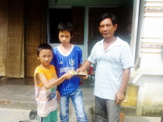 Hai em Nguyễn Văn Khởi (trái) và Nguyễn Lê Khiêm (giữa) trả lại chiếc ví cho ông Hòa.