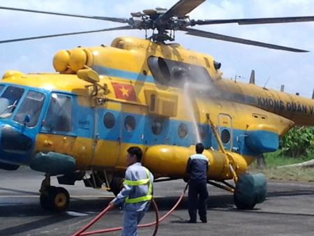 Nhân viên sân bay phun nước làm nguội trực thăng sau 3 giờ bay tìm kiếm (Ảnh: Huỳnh Hải)