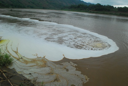 Cận cảnh họng nước thải đang phụt dòng nước có bọt màu trắng ra sông Hồng.