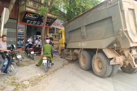Bánh xe may mắn sa xuống cống nước thải, giữ cho xe không lao thẳng vào cửa hàng sơn