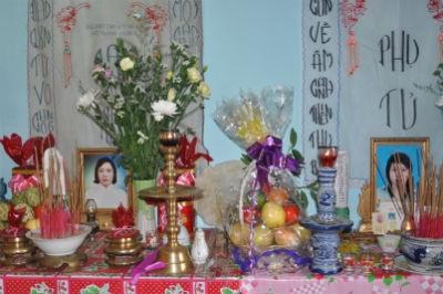 Di ảnh của nạn nhân (bên phải) đặt bên di ảnh mẹ