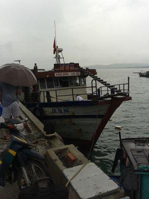 Nhiều hành khách tranh nhau lên tàu kém chất lượng để về đất liền trong điều kiện mưa lớn