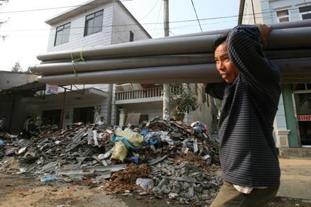 Một người dân đang bê ống nước bên cạnh đống đổ nát hiện diện khắp thị trấn.