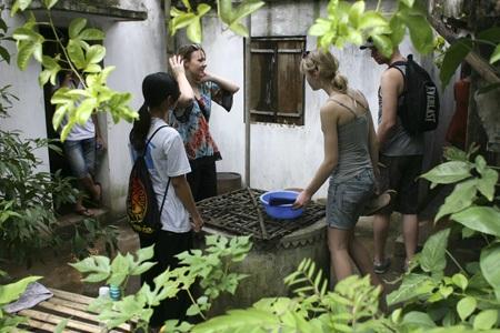 Các khách tham quan đang quan sát chiếc giếng khơi của người Việt.
