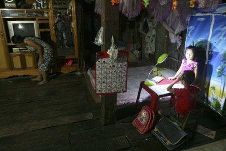 Chị Vi Thị Viết, dân tộc Thái đang tắtti viđểcác con học bài.