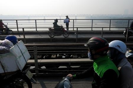 Một nữ sinh viên kiên trì đứng xin rác giữa trời nắng trên cầu.