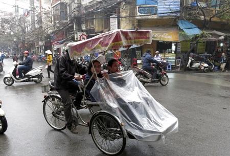 Dạo phố trên xích lô áo mưa.