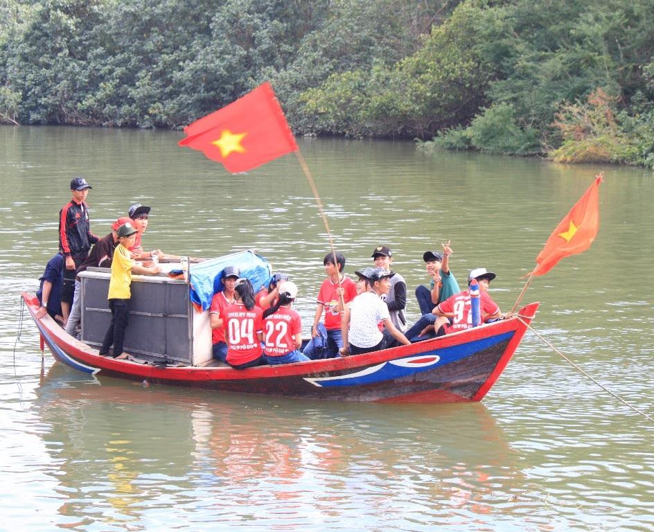 Dưới sông một số cổ động viên nhí cổ vũ nhiệt tình cho các đội thi