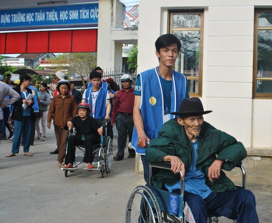 Các thiện nguyện viên giúp người già đi lại khó khăn đến khu vực khám bệnh
