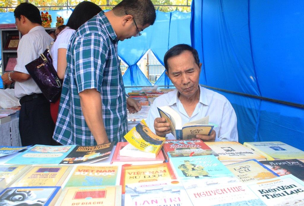 Một độc giả lớn tuổi đang nghiên cứu với gian sách lịch sử Việt Nam qua các thời kỳ