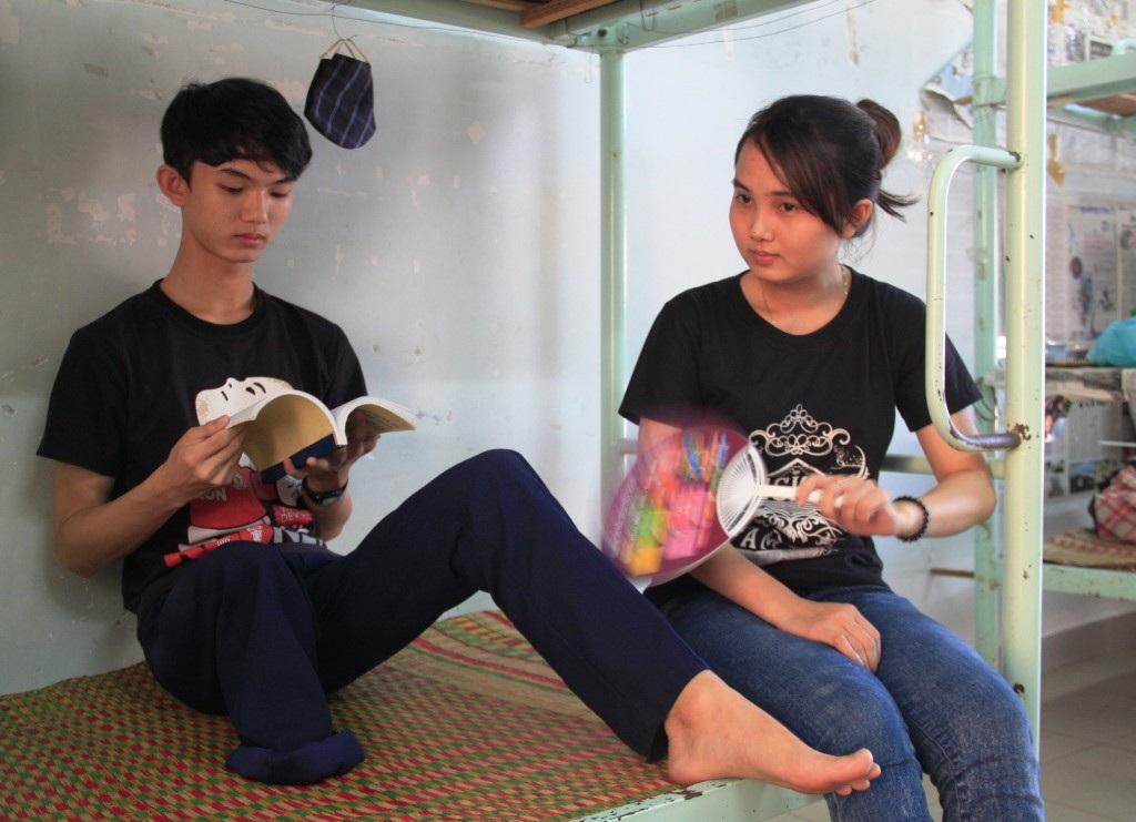 Trần Thị Như Phượng ngồi quát mát cho cậu em trai dị tật ngồi ôn bài.