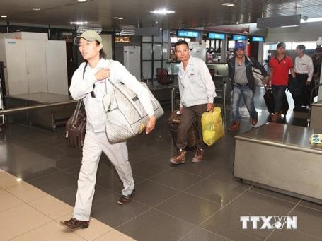 Những lao động Việt Nam từ Libya về nước ra cửa Sân bay quốc tế Nội Bài. (Ảnh: Anh Tuấn/TTXVN)
