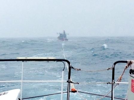 Tàu cứu hộ đang lai dắt tàu của ngư dân bị nạn vào bờ