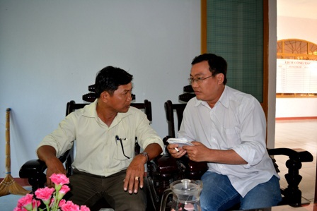 Chủ tịch xã Quế An – ông Hoàng Kim Minh (ảnh trái) trao đổi với PV