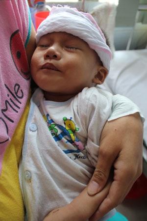 Thỉnh thoảng bé Bảo mắt lại nhắm nghiền nhưng sự đau đớn thể hiện rõ trên khuôn mặt