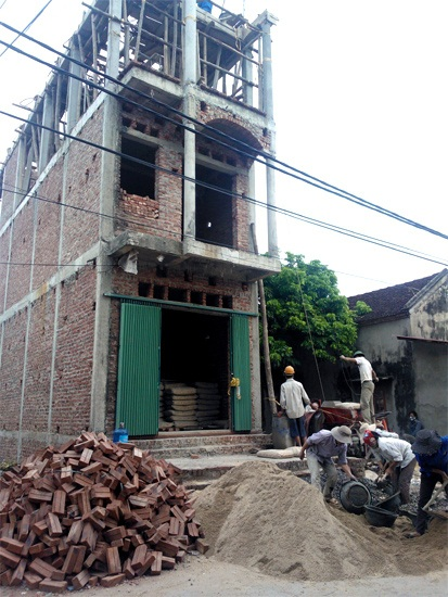 Một ngôi nhà ở giữa làng Ải của gia đình chị Tám đi bán xôi, ngô đang được xây khang trang