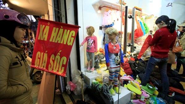 Người dân lựa chọn quần áo giảm giá cuối năm trên phố Phan Đình Phùng (Hà Nội). Ảnh: Như Ý
