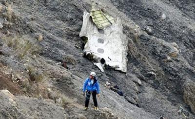 Một nhân viên cứu hộ đứng cạnh một mảnh vỡ của chiếc máy bay Airbus A320 nằm trên hẻm núi dốc đứng