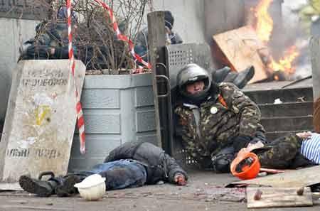 """Một người biểu tình ngồi cạnh thi thể của hai """"đồng đội"""" chết vì đạn bắn tỉa hôm 20/2 (ảnh: Getty)"""