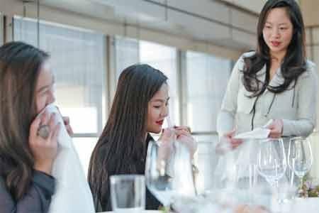 Ho (phải) dạy các học viên giàu có dùng khănlau miệng một cách lịch thiệp