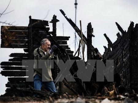Người dân địa phương thu dọn căn nhà bị đổ nát trong xung đột tại Donetsk ngày 6/4 vừa qua. (Ảnh: