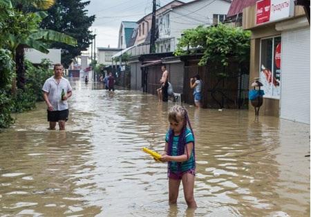 Trẻ em chơi trên đoạn đường ngập nước.