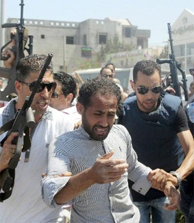 Cảnh sát áp giải một người bị tình nghi có liên quan đến vụ tấn công khách sạn ở Tunisia.