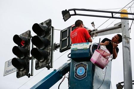 Công an Trung Quốc mặc thường phục đang lắp camera theo dõi trên đường phố Campuchia. (Ảnh: