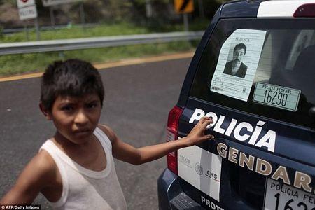Một cậu bé Mexico đứng sau chiếc xe cảnh sát có dán yết thị truy nã trùm El Chapo (Nguồn: