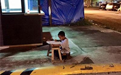 Xót xa cậu bé ngồi học dưới ánh đèn le lói hắt ra từ phía nhà hàng.