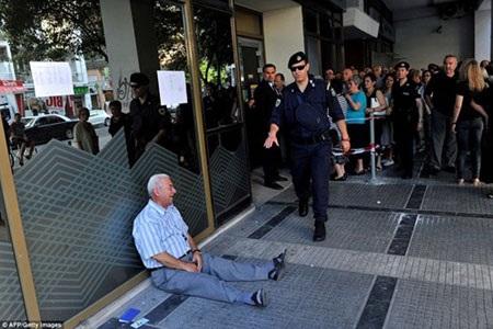 Ông Giorgos Chatzifotiadis đau khổ ngồi sụp xuống nền, bên cạnh là sổ lương hưu và chứng minh thư.
