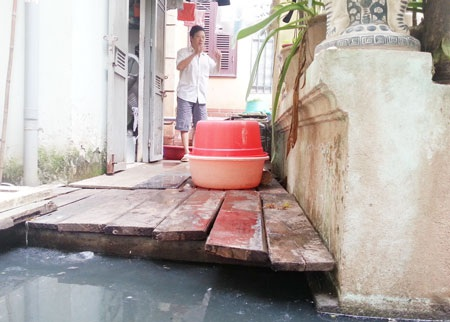 Gia đình ông Tuấn phải xếp gỗ cao hàng mét để làm lối đi luôn ngập ngụa nước thải.