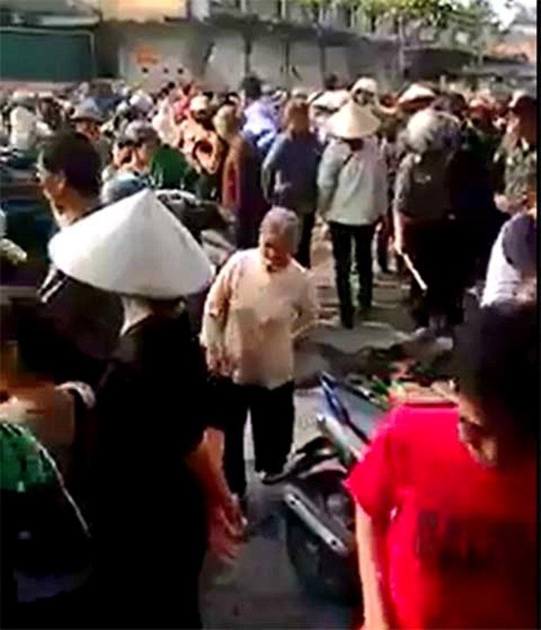 Người dân tụ tập phản đối việc người phụ nữ bán hàng bị trói tay ( ảnh cắt từ clip)