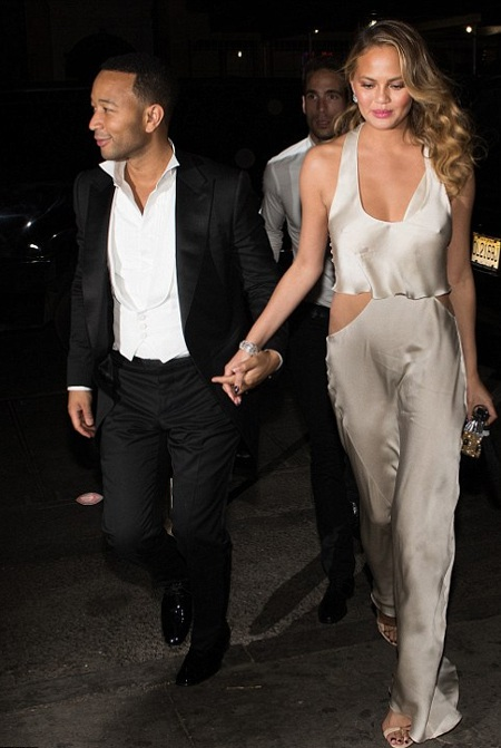 Vợ chồng John Legend nắm tay nhau tới tham dự tiệc đêm.