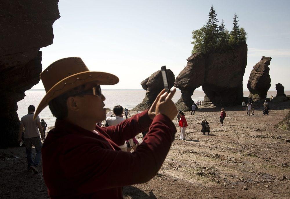 Du khách dừng lại chụp ảnh khối đá Hopewell trên vịnh Fundy, New Brunswick. (Nguồn: Sputniknews)