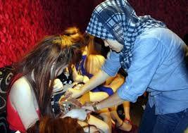 Một nhân viên công vụ Malaysia kiểm tra giấy tờ của những phụ nữ nhập cư trái phép vào nước này.