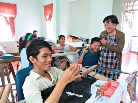 """Chị Liền bên """"các con"""" ở cơ sở dạy nghề tranh thêu cho trẻ khuyết tật Thanh Ngọc Minh"""