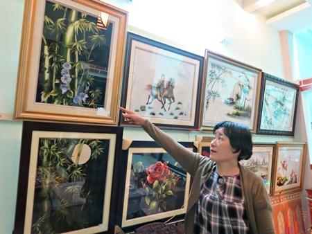 Chị Liền tự hào khoe những tác phẩm tranh thêu đẹp của học trò.