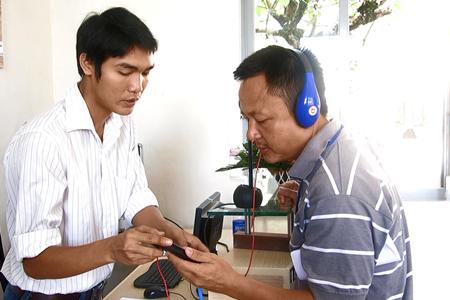 Nhân viên kỹ thuật hướng dẫn du khách tham quan Bảo tàng sử dụng thiết bị thuyết minh tai nghe