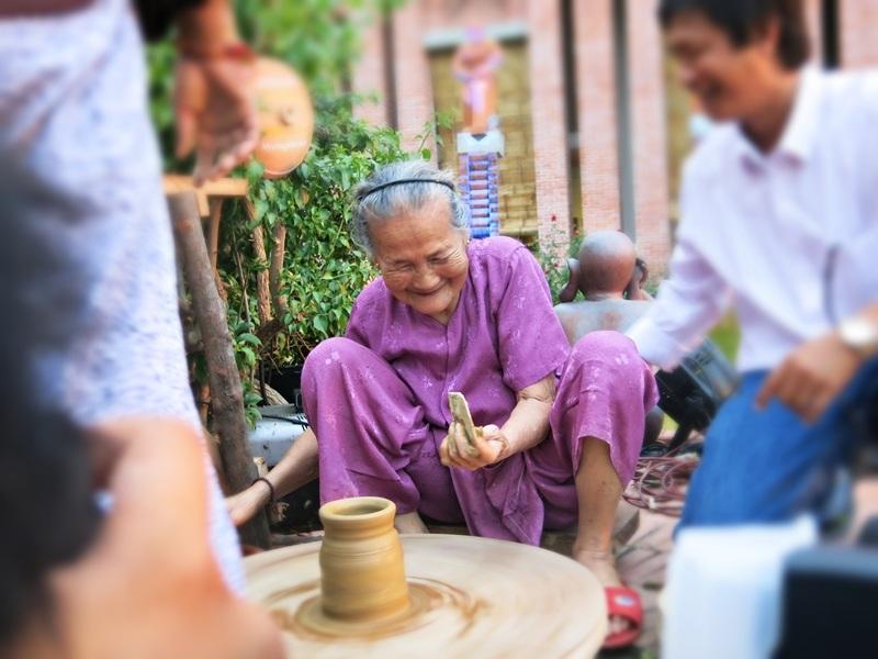 Nghệ nhân Nguyễn Thị Được chuốt sản phẩm gốm đầu tiên ở Công viên đất nung vừa hoàn tất giữa làng