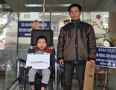 Hai bố con bé Minh nhận quà bạn đọc Dân trí tại khoa Phẫu thuật cột sống, BV Việt Đức.