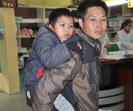Chưa thể đi lại được nên Minh được bố cõng lên viện khám bệnh.