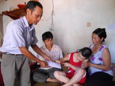 Đại diện chính quyền địa phương trao quà bạn đọc đến gia đình cháu Trang.